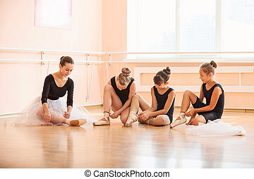 bailarinas, sapatos balé, sentando, chão, jovem, enquanto, pôr, classe, pointe