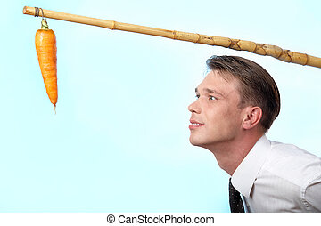 Portrait of businessman looking at fresh carrot on angle