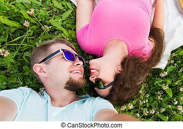 baixo, conceito, par, amor romântico, selfie, -, cima, jovem, capim, ternura, verde, atraente, fim, deitando, vista superior