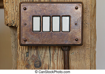 Closeup of vintage bake lite toggle light switch in brown on wooden pole