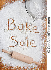 Flour on a wooden table symbolising a Bake Sale Notice