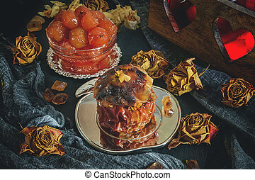 Baked Apple with nuts, honey and Apple jam for tea on the background of the candle holder with hearts.