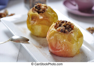 Baked apples on white plate with cup of tea