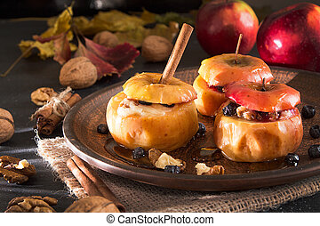 Baked apples stuffed with walnuts and honey on on brown plate