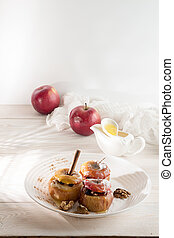 Baked apples stuffed with walnuts and honey on white plate