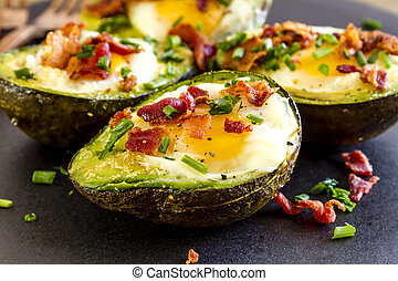 Baked avocado and eggs boats with bacon crumbles and chives. Low carb high fat breakfast