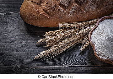Baked brown bread bunch of wheat rye ears wooden bowl with flour
