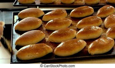 Baked buns on oven tray. Manufacturing process of baking...