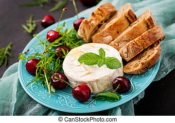 Baked Camembert cheese, toast and arugula salad with sweet cherries.