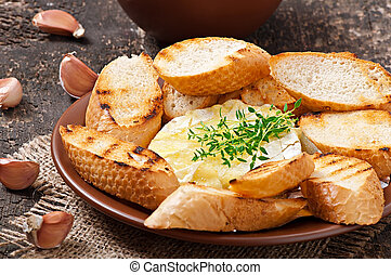 Baked Camembert cheese with thyme and toast rubbed with ...