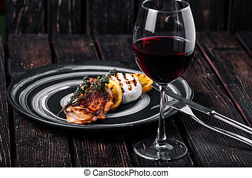 Baked Camembert with caramelized orange and grilled chicken on wood background. Glass of red wine on the table