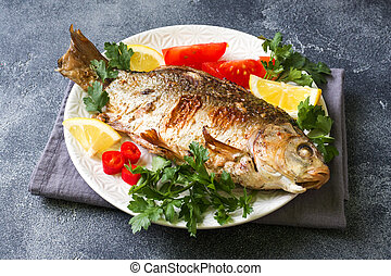 Baked carp fish with vegetables and spices on a plate on a...