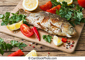 Baked carp fish with vegetables and spices on a wooden table.