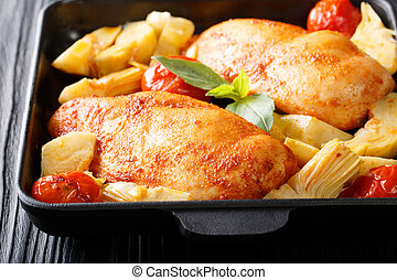 Baked chicken fillet with artichokes and tomatoes closeup. horizontal