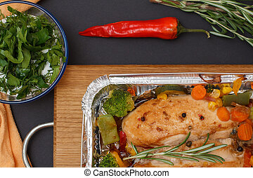 Baked chicken or fillet in metal container with vegetables on cutting board.