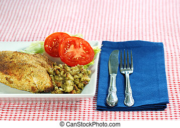 Baked chicken with stuffing and knife fork