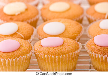 Baked cupcakes with sweet button shaped fondant topping on a cooling rack.