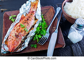 baked fish in the foil and on a table