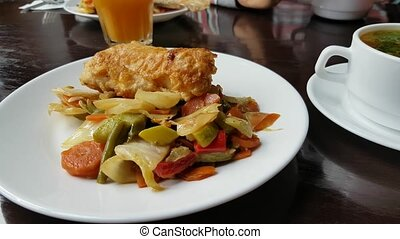 Baked fish with vegetables and soup in restaurant
