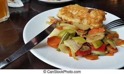 Baked fish with vegetables in restaurant