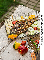 Baked fish with vegetables, on a wooden background