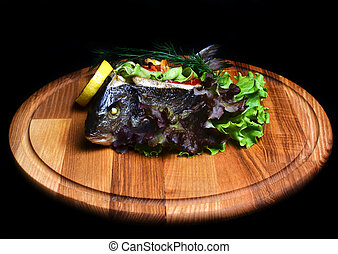 Baked fish with vegetables on a wooden board.