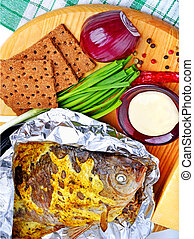 Baked fish with vegetables, sauce, red pepper, crisp bread on cutting board