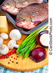 Baked fish with vegetables, sauce, red pepper on cutting board