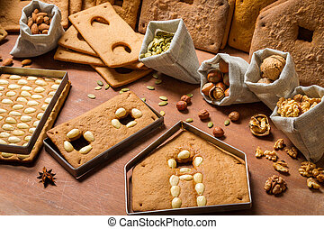 Baked gingerbread cottage elements with the ingredients for decoration