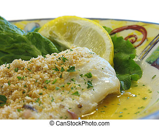 Baked haddock with cracker crumbs and a lemon for garnish.