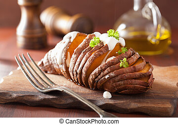 Baked hasselback potato with sour cream