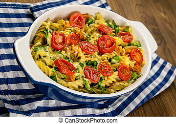 Baked homemade pasta fusilli with bacon and cream, spinach and fresh cherry tomatoes on the napkin stand on wooden table. Front views close-up