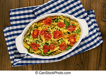 Baked homemade pasta fusilli with bacon and cream, spinach and fresh cherry tomatoes on the napkin stand on wooden table. Top views close-up