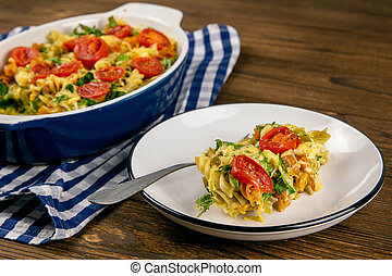 Baked homemade pasta fusilli with bacon and cream, spinach and fresh cherry tomatoes stands in a plate with a fork, stand on wooden table. Top views close-up