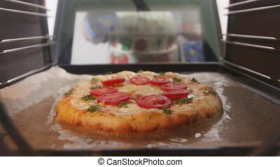 Baked italian pizza in convection oven. Woman opens cooker...
