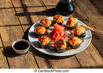 baked Japanese rolls in a white plate on an old wooden table