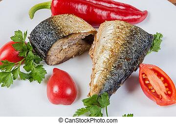Baked mackerel slices, fresh vegetables, parsley closeup in selective focus