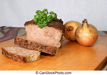 baked meat loaf with organic parsley on a timber board