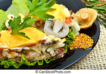 Baked meat with cheese, mushrooms vegetables and rosmarin on bla