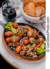 baked meat with vegetables on a wooden stand