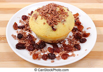 Baked muffins with grated chocolate and heap of raisins on white plate