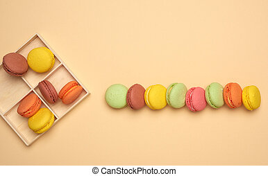 baked multi-colored macarons cookies lie in a row on a beige background, top view