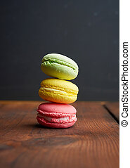 baked multi-colored macarons cookies on a brown wooden background