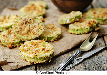 baked parmesan zucchini crisps on a dark wood background....