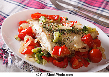 Baked plaice with seasonal vegetables close-up on a plate on...