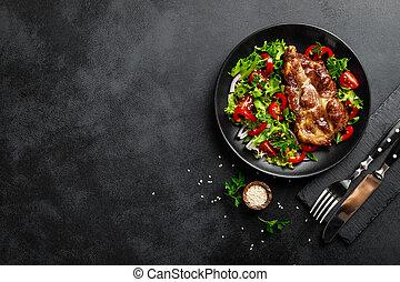 Baked pork steak with fresh vegetable salad on a plate