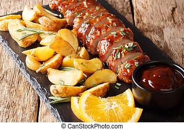 baked pork tenderloin with rosemary in honey-orange sauce served with potato wedges closeup on a plate. horizontal