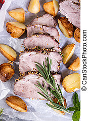 Baked potato, cold-boiled pork meat, rosemary and basil over on white parchment. Top view.