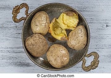 Baked potato in a metal bowl on a wooden table, simple vegetarian food. Boiled potatoes on wooden table, close up