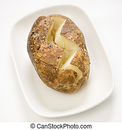 Baked potato. - Plain baked potato sliced down the middle on...
